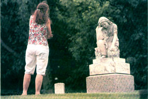 Woman looking at angel grave marker of teenage girl